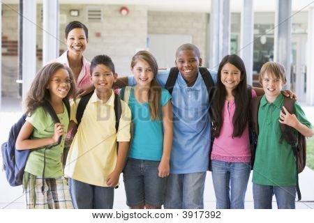 Six Students Standing Outside School With Teacher