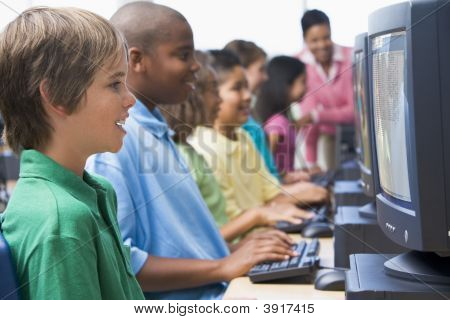 Six Children At Computer Terminals With Teacher In Background (Depth Of Field/High Key)