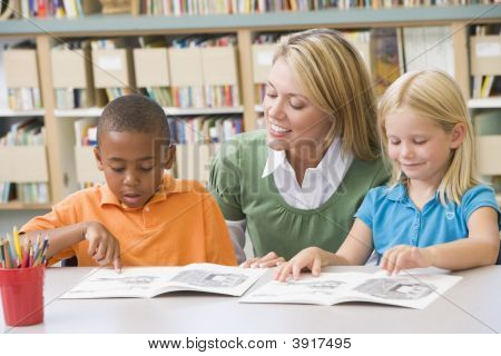 Two Students In Class Reading With Teacher