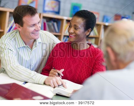 Man And Woman Sitting In Library Near Another Man With A Book And Notepad (Selective Focus)