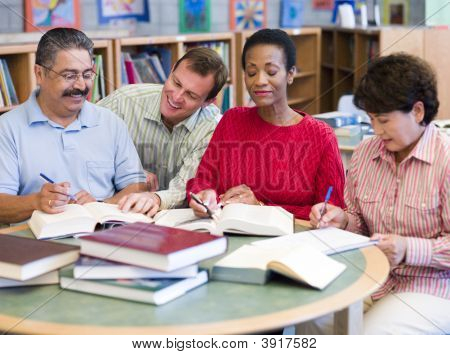 Four People In Library With Books And Notepads (Selective Focus)