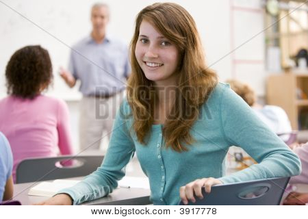 Female Student With Other Students In Classroom