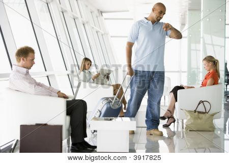 Male Airline Passenger Waiting With Other Passengers In Departure Gate