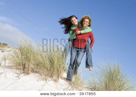 Young Woman Giving Piggyback Ride To Her Friend On A Sand Hill