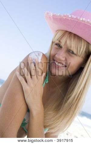 Woman On Beach Applying Sunblock Lotion To Her Shoulder