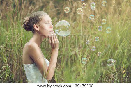Porträt von schönen blonden Mädchen beginnt Seifenblasen im Feld