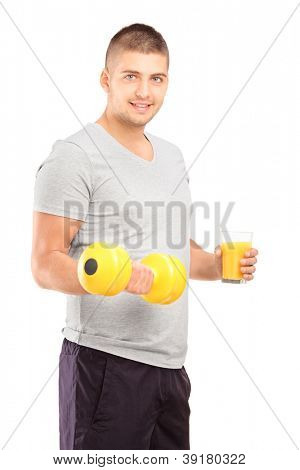 Young man holding a dumbbell and glass of fresh orange juice isolated on white background