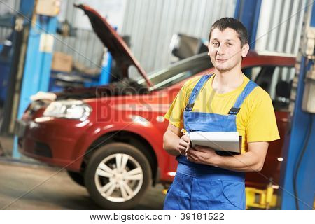 repairman auto mechanic with clipboard in front of modern car during automobile maintenance at engine auto repair shop service station