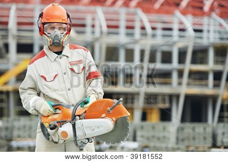 construction worker in safety protective equipment with petrol disc cutter