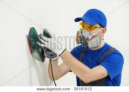 Home improvement worker in protective mask and glasses working with sander for smoothing wall surface