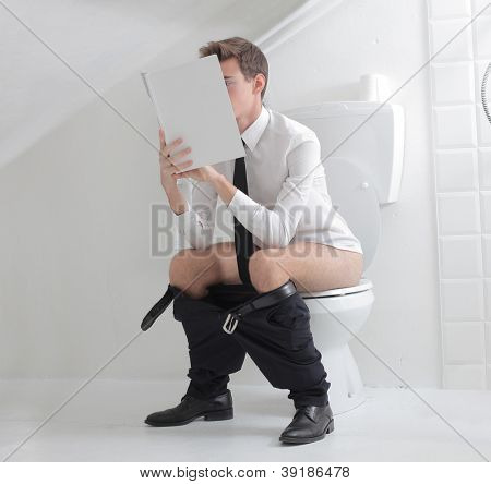 Young man in tie reading a magazine on a toiler