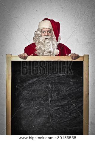 Santa Claus holding a blackboard