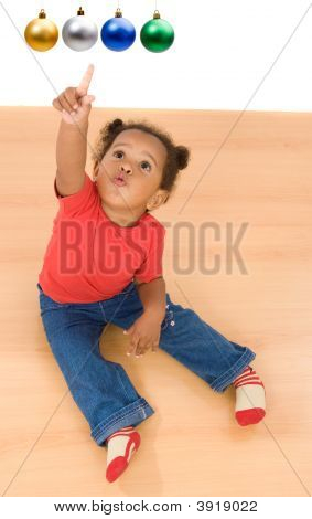 African Baby Girl Pointing Four Balls Of Christmas