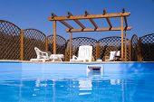 foto of pergola  - Wooden pergola viewed from sparkling fresh swimming pool - JPG