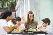 stock photo of tweenie  - Family at restaurant eating and smiling  - JPG
