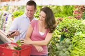 image of grocery-shopping  - Young couple shopping for broccoli at a grocery store - JPG