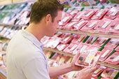 picture of grocery store  - Man shopping for meat at a grocery store - JPG