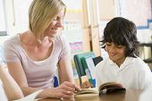stock photo of girl reading book  - Student in class reading book with teacher - JPG