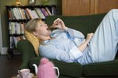 stock photo of saddening  - Young woman lying on sofa at home eating chocolate - JPG