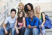 stock photo of ethnic group  - Six people sitting on staircase outdoors smiling - JPG