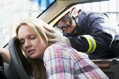 foto of accident victim  - Fireman helping a woman after she got in an accident - JPG