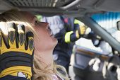 foto of crew cut  - Injured woman in car with firefighter in background cutting out windshield  - JPG