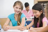 stock photo of tweeny  - Students in class writing with teacher in background  - JPG