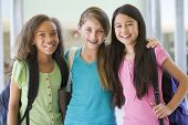 stock photo of tweenie  - Three students standing outside school together smiling  - JPG
