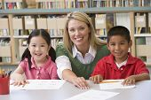 stock photo of teachers  - Two students in class with teacher - JPG