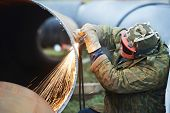 pic of pipe-welding  - Construction Welder worker in protective glasses cutting metal pipe at building site with welding flame torch cutter - JPG