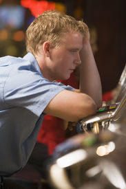 stock photo of slot-machine  - Man in casino playing slot machine frustrated with people in background  - JPG