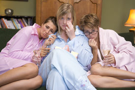 foto of sad face  - Three woman in night clothes sitting at home watching sad movie on TV - JPG