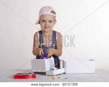 Girl twists nut pliers, repairing toy