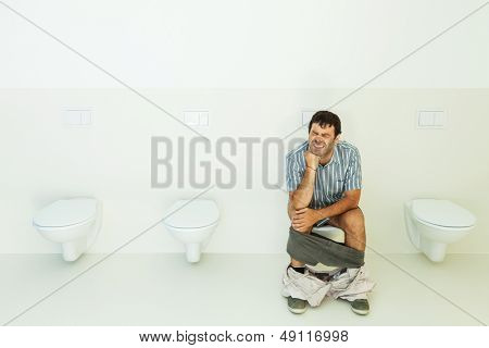 Man sitting on the toilet, public bathroom
