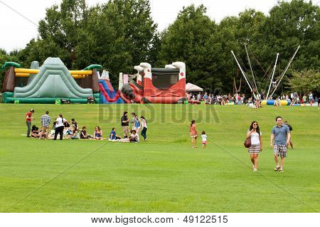 People Enjoy Activities And Relaxing On Grass At Summer Festival