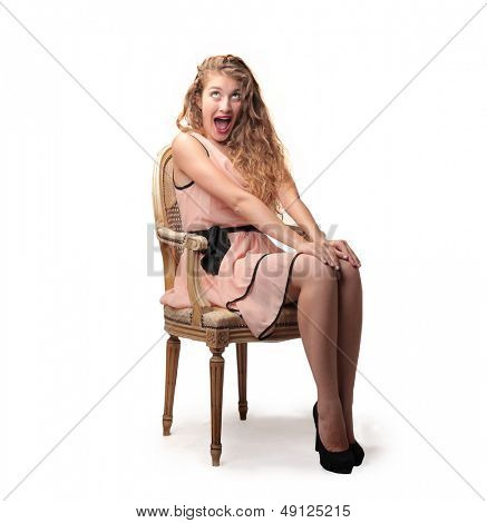 surprised beautiful girl sitting on an old chair