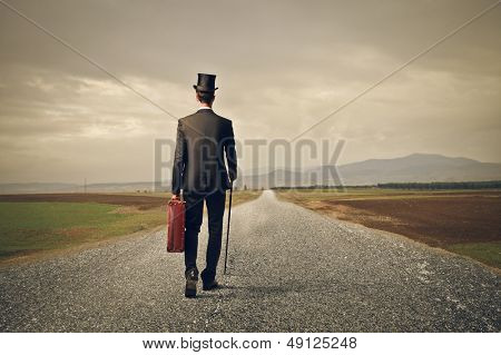 elegant man with cylinder and suitcase walking in a deserted road