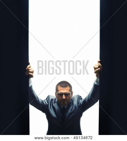Coming confident businessman by opening some gate