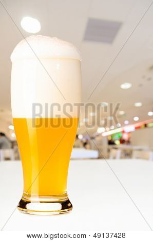 glass of fresh draft unfiltered beer on table in cafe