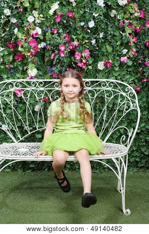 Little cute girl sits on bench and swing legs near verdant hedge.