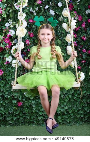 Happy little girl with shamrocks on head in green sit on swing in garden next to verdant fence.
