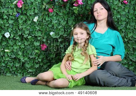 Young mother and little daughter sit on grass in garden next to verdant fence.