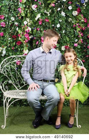 Happy father looks at little daughter sitting on white retro bench near verdant hedge.