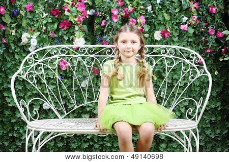 Little happy girl sits on white retro bench near verdant hedge.