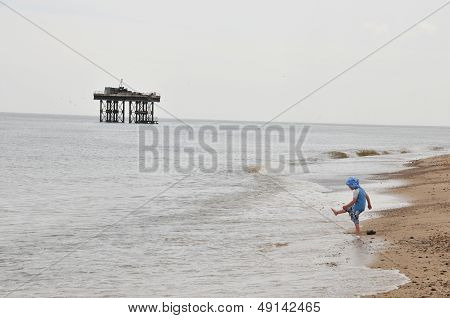 Small child kicking sand on a beach