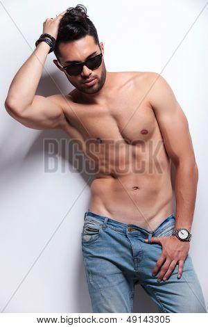 joven topless mirando hacia abajo mientras pasa su mano por su cabello y sosteniendo su pulgar en el
