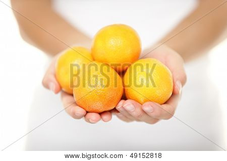 Clementine. Clementines that are a variety of mandarin oranges citrus fruits. Woman showing handful. Shot in studio with shallow depth of field isolated on white background.