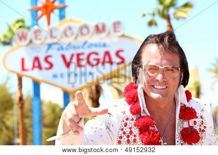 Elvis impersonator man in front of Las Vegas on the strip pointing looking at camera. People having fun and Viva Las Vegas concept with Elvis look-alike