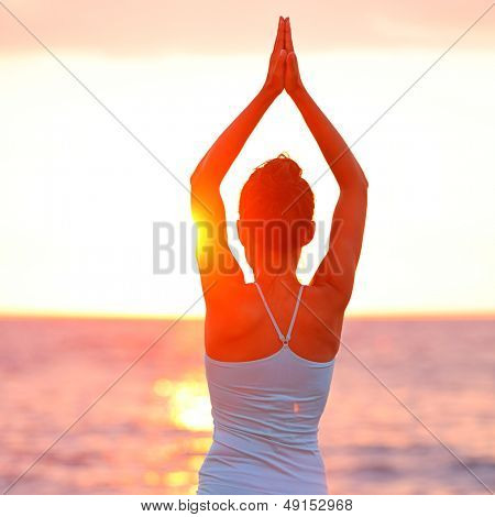 Meditation Yoga woman meditating at beach sunset or sunrise relaxing in yoga pose. Serene relaxed female yoga instructor in calm nature sea scene. From Big Island, Hawaii, USA.