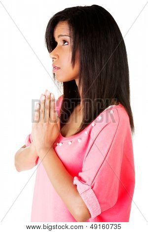 Young pretty woman praying, over white background.